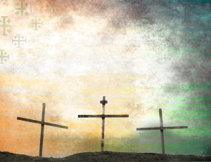 Three crosses on a hill with a beautiful sky in the background.